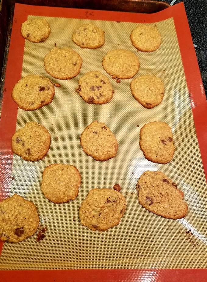 Oatmeal cookies with chocolate chips or raisins on a cookie sheet lined with a silpat mat