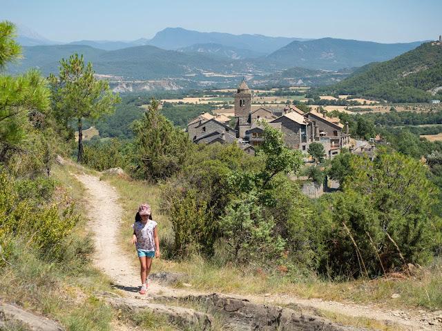 Niña andando por un camino en la montaña con el pueblo de Sieste al fondo