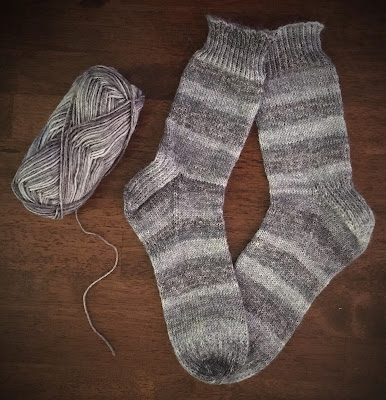 Socks knitted with DROPS Fabel in Silver Fox on table