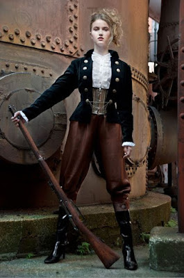 An example of waist cinchers aka waspies used in women's steampunk fashion. This woman wears her waist cincher with a ruffled blouse, jacket, pants and boots.