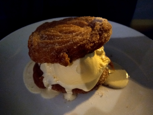 Two churro basis filled with ice cream over a white plate.