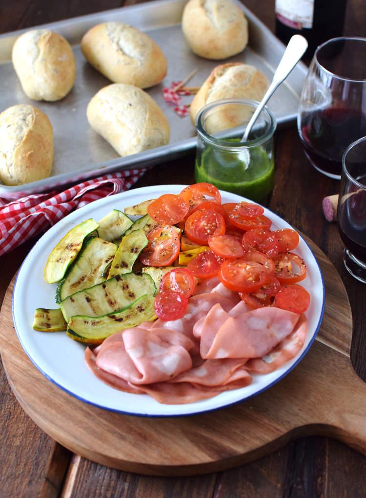 Mortadela italiana, calabacín asado al grill, tomates frescos y pan rústico, ingredientes para hacer sándwich