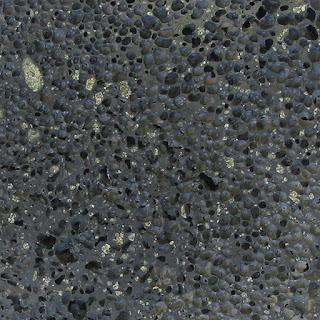 Basalto vescicolare con evidenti fenocristalli di olivina verdi-giallastri.
