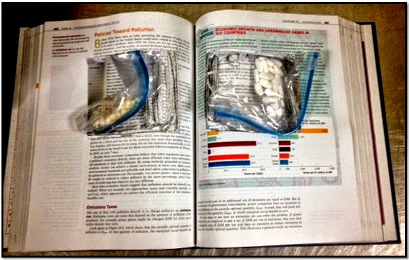 A plastic bag containing 67 pills hidden inside of a hollowed out textbook was discovered in checked baggage at Philadelphia International Airport (PHL).