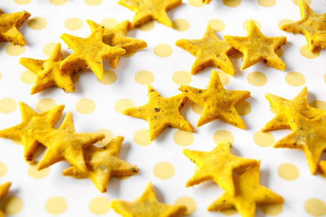 Golden homemade dog treats shaped like stars on a yellow polka dot table cloth
