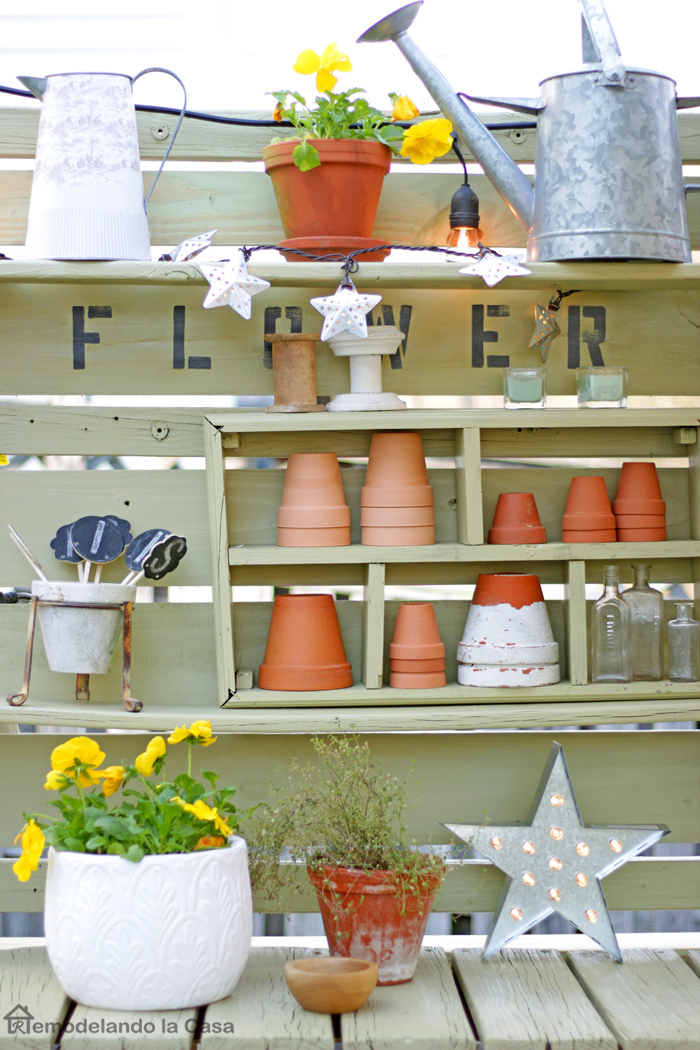green painted potting benches with terracotta pots