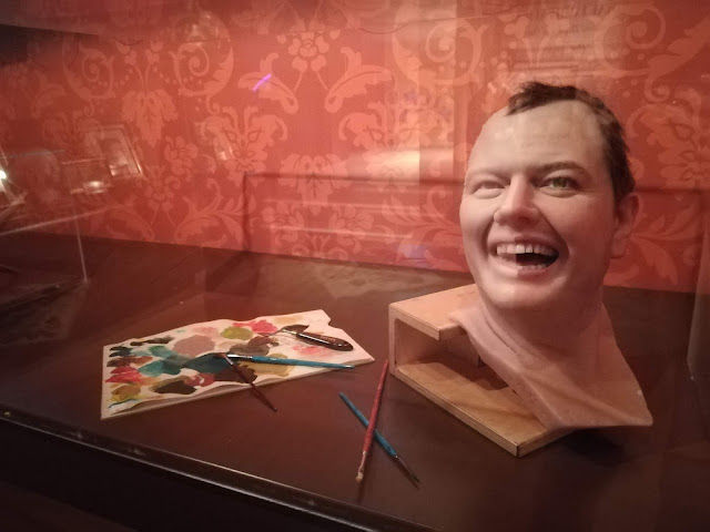 a waxwork head of the comedian Alan Carr, half bare and half painted