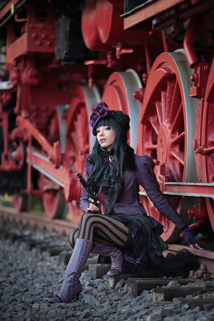 woman wearing steampunk gothic victorian clothes in purple and black. steamgoth style, top hat, skirt, jacket, striped stockings, boots, gun