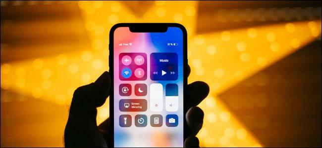 يد تمسك بجهاز iPhone X مع فتح مركز التحكم.