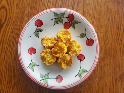 oak kitchen table with small ceramic plate painted with cherries. On the plate are 5 round cauliflower tots that resemble tiny muffins.