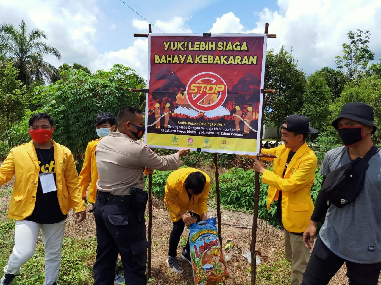 Cegah Karhutla, Bhabinkamtibmas Polsek Kahayan Tengah Bersama Mahasiswa KKN Pasang Spanduk Siaga Bahaya Kebakaran