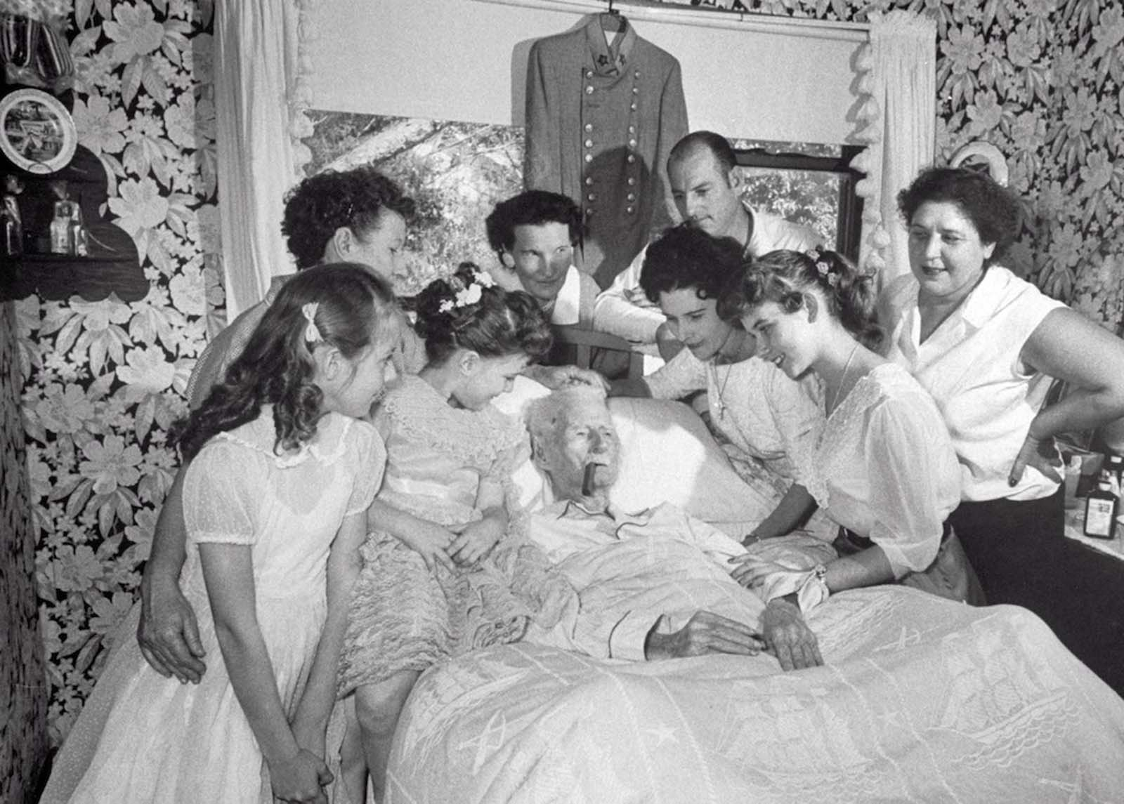Walter Williams lying in bed with cigar, surrounded by family and friends. 1959.