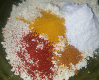 Mixing besan with corn flour, red chilli powder, turmeric powder and carom seeds for the batter of bread pakora