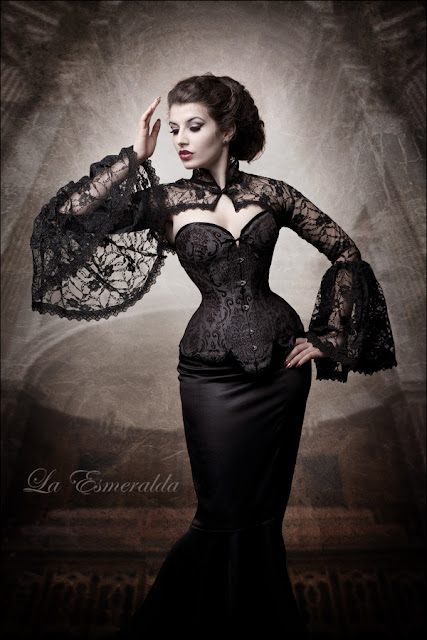 Woman wearing neo-victorian clothing. Black overbust longline corset, skirt and lace bolero.