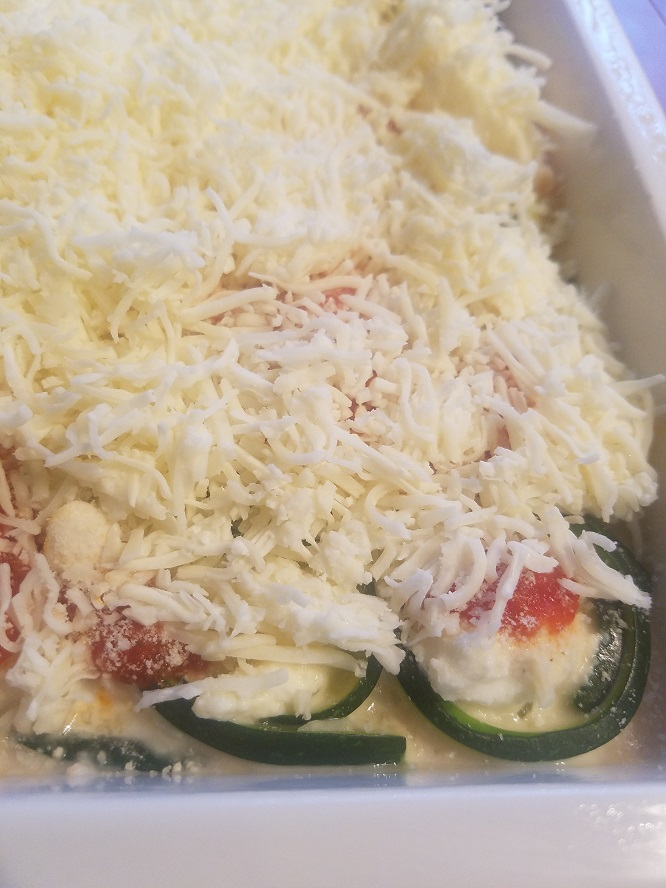 this is a zucchini stuffed with ricotta cheese in a white casserole dish topped with mozzarella melted cheeses and golden brown