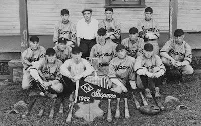 Black & white photo of men in baseball uniforms. Pennant in front says P&R Shopmen 1922