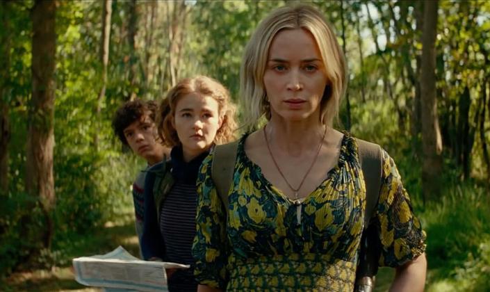 Imagem de capa: a personagem de Emily Blunt em Um Lugar Silencioso, na frente, com uma mochila, um rifle e um mapa, sendo seguida por suas duas crianças: um menino e uma menina, com diversas árvores ao fundo.