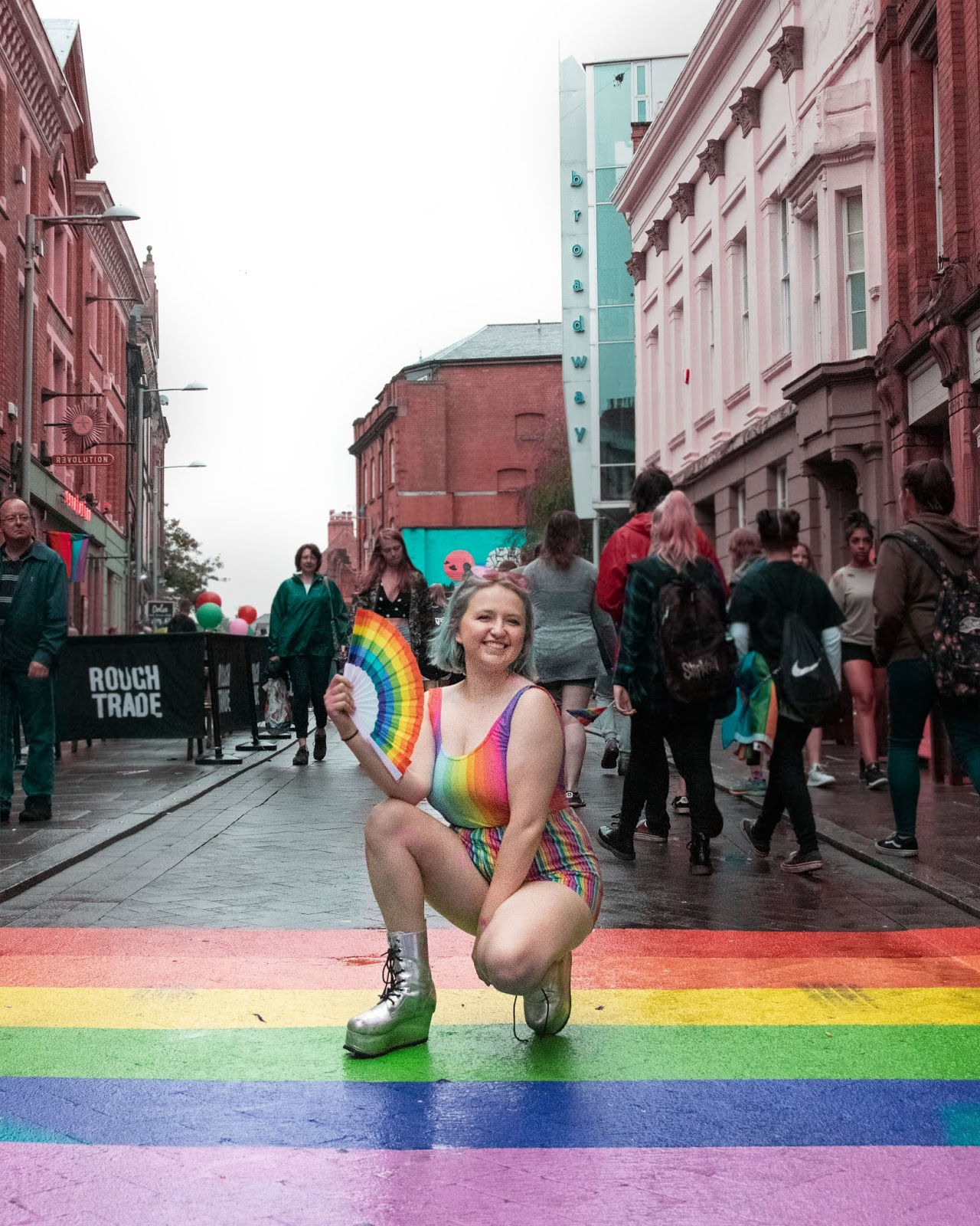 Me, Crouched in the centre of a rainbow crossing holding a fan and wearing rainbow clothing