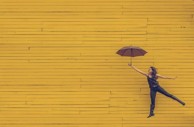 woman with pink umbrella jumping high against yellow wall