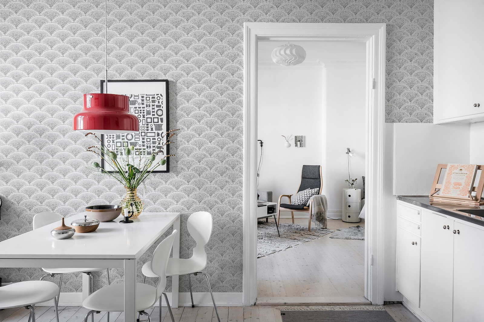 White kitchen design inside of a small scandinavian interior, pattern wallpaper, red retro lamp