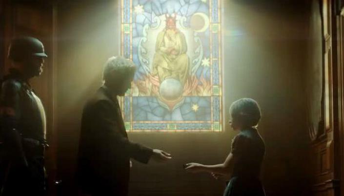 Imagem: fundo de uma igreja com uma janela de vitral com uma figura de um demônio sentado em um trono com chamas e fundo azul acima da parede, a janela iluminando o personagem de Owen Wilson, um homem em um terno marrom ao lado de uma garotinha em roupas maltrapilhas e um oficial da A.V.T. em uma roupa preta de agente com capacete e proteção.