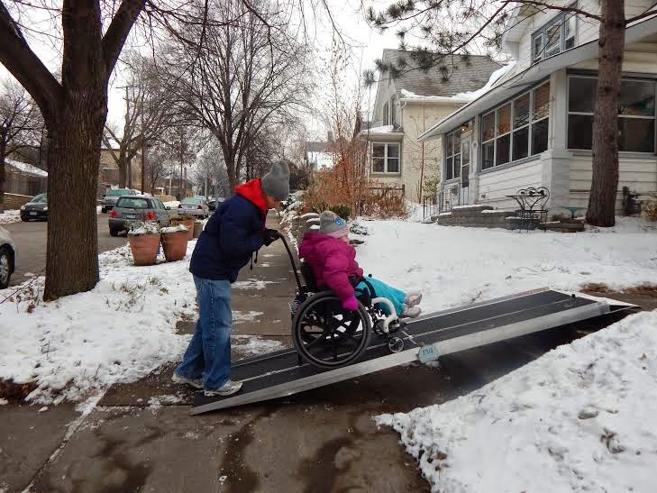 Wheelchair ramp being used in winter by elderly people.