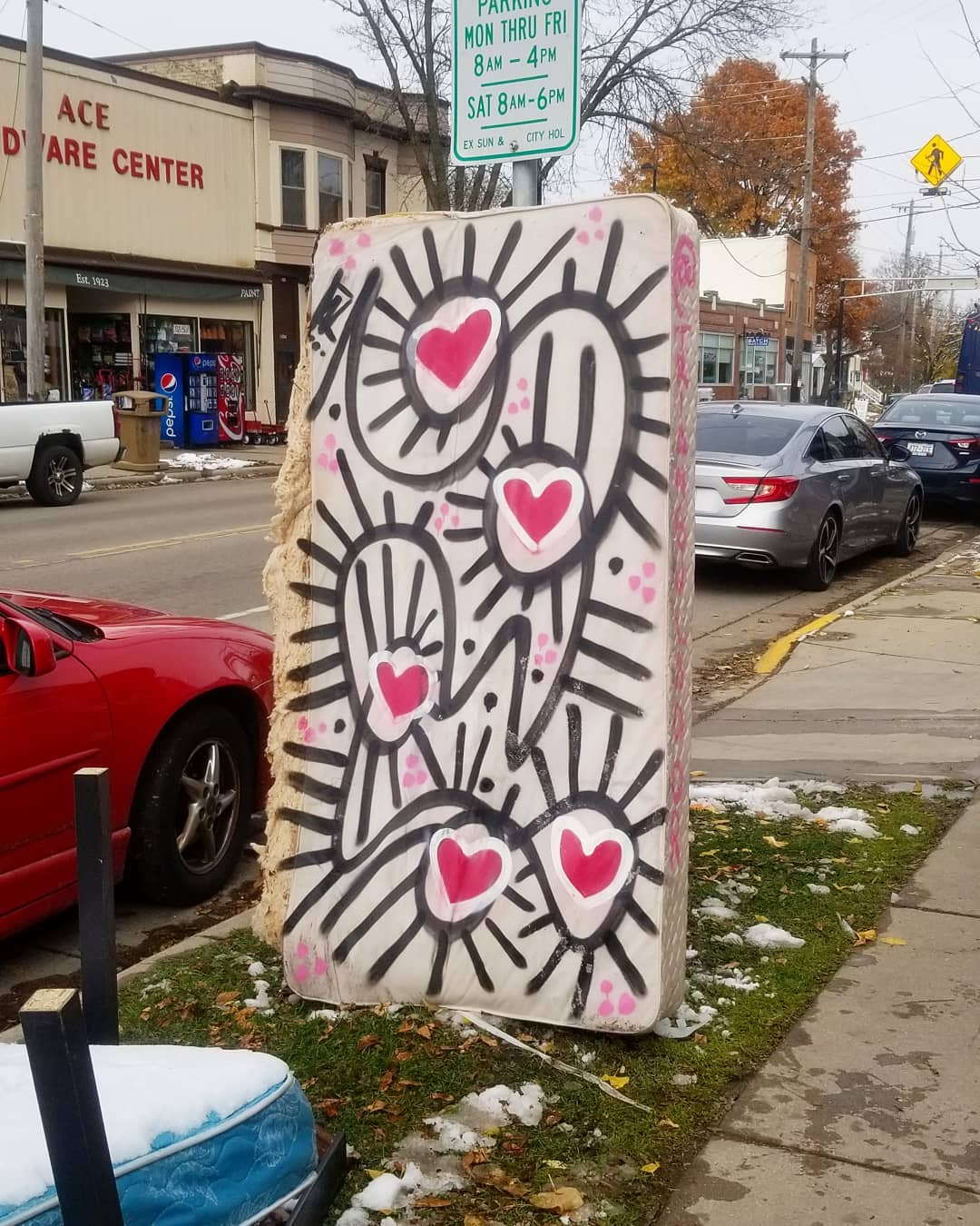 Image contains street art outdoors on box spring next to car