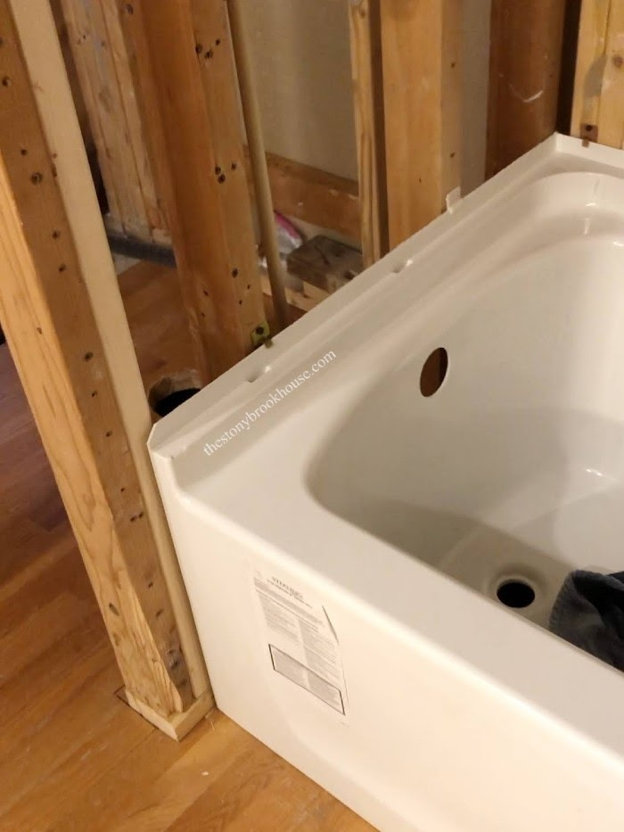 Adding clips to tub to secure to wall