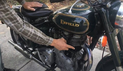 Pointing to the motor of a Royal Enfield motorcycle.