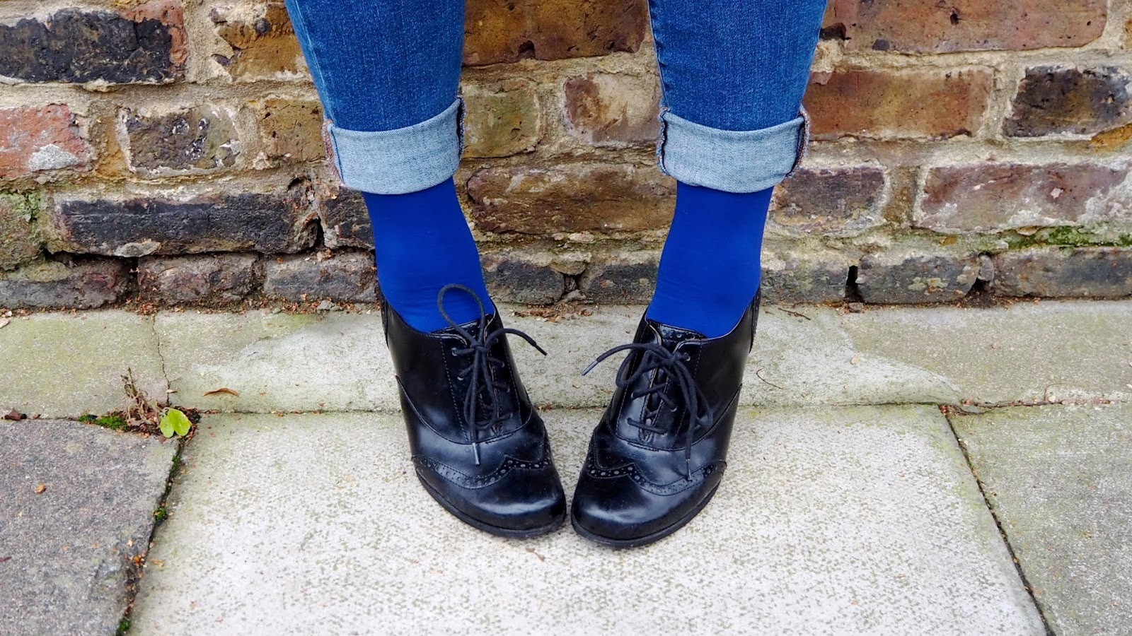 rolled up skinny jeans, royal blue socks, black brogues in front of a brick wall
