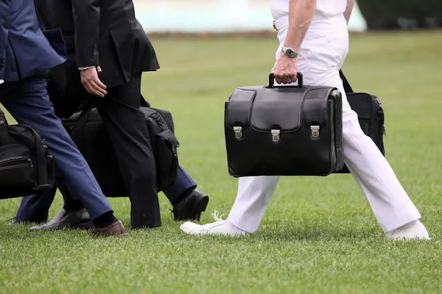 """An aide carrying a """"nuclear pair"""" steps aboard Marine One helicopter with former President Donald Trump before flying from the White House to Florida on May 8, 2019. Photo: Reuters"""