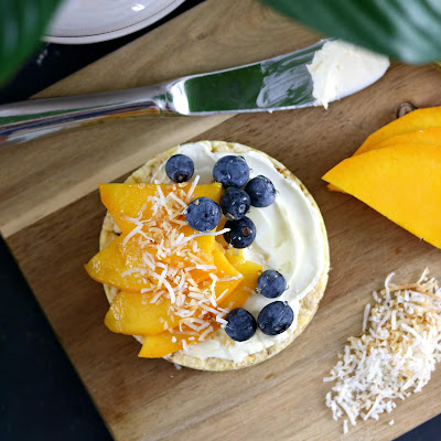 Healthy Rice Cake Topping Ideas - Rice Cake with Cream Cheese Honey Coconut Mango Slices and Blueberries on Wooden Chopping Board