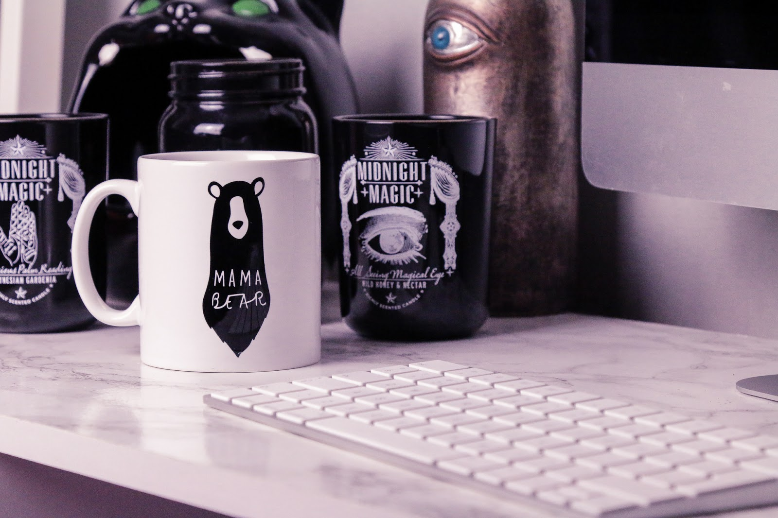 """Close up photo of a white mug that has a photo of a black bear on it that has writing that says """"mama bear"""" sitting on a white marble desk top next to a silver keyboard and black candles."""