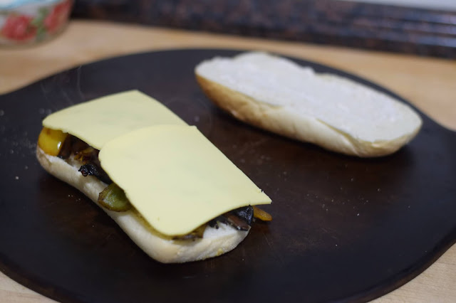 Vegan cheese being added to the mushroom philly.