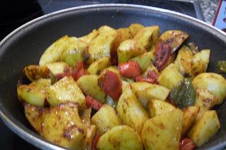 Añadiendo las patatas al sofrito de pimientos y gambas
