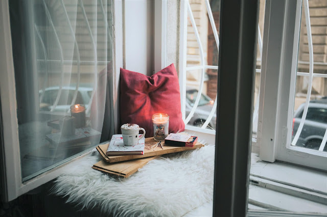 Image is of an open window. On the ledge is a pillow, book, candle and a warm drink