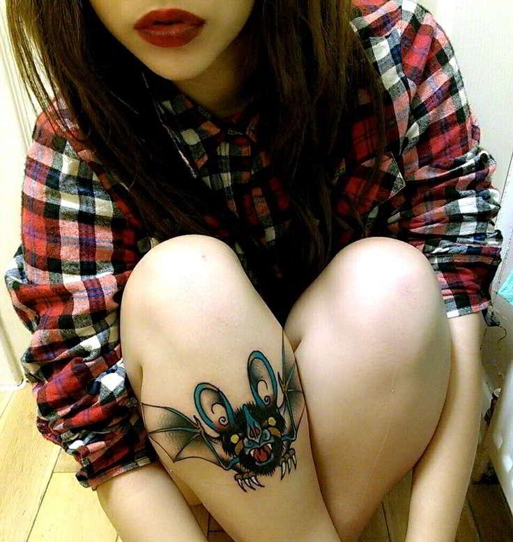 Un tatuaje de murcielago en la perna de una modelo