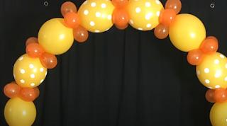 Freistehender Ballonbogen mit gelb-orangefarbenen Luftballons.