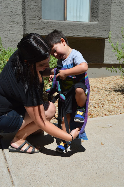 Image of fair skin dark haired woman placing toddler's legs into shoulder straps of purple rainbow Onbu