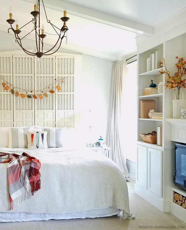 Fall decor in bedroom with tall headboard, built-ins and white decor