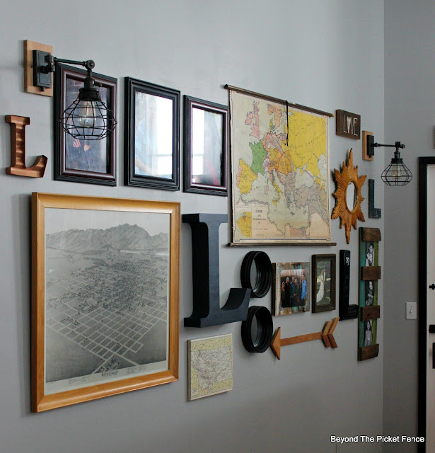 An eclectic gallery wall with old maps and marquee letters