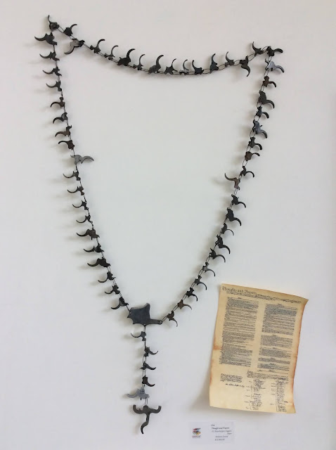 """""""Thoughts and Prayers"""" Rosary made of 61 recycled used gun triggers."""