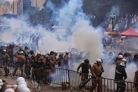 A foto mostra os soldados covardemente jogando bombas de gás lacrimogênio sobre os professores.