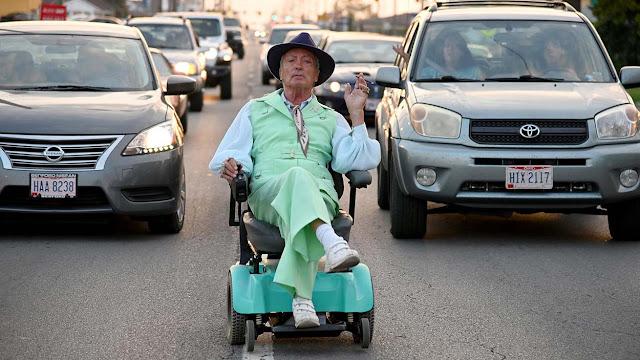 Udo Kier riding a rascal down the street