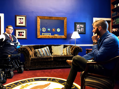 """A man in a power wheelchair is speaking to a congressional staff member. They are in a congressional office. A rug underneath them bears a seal and says: """"U.S. House of Representatives."""" The walls are dark blue."""