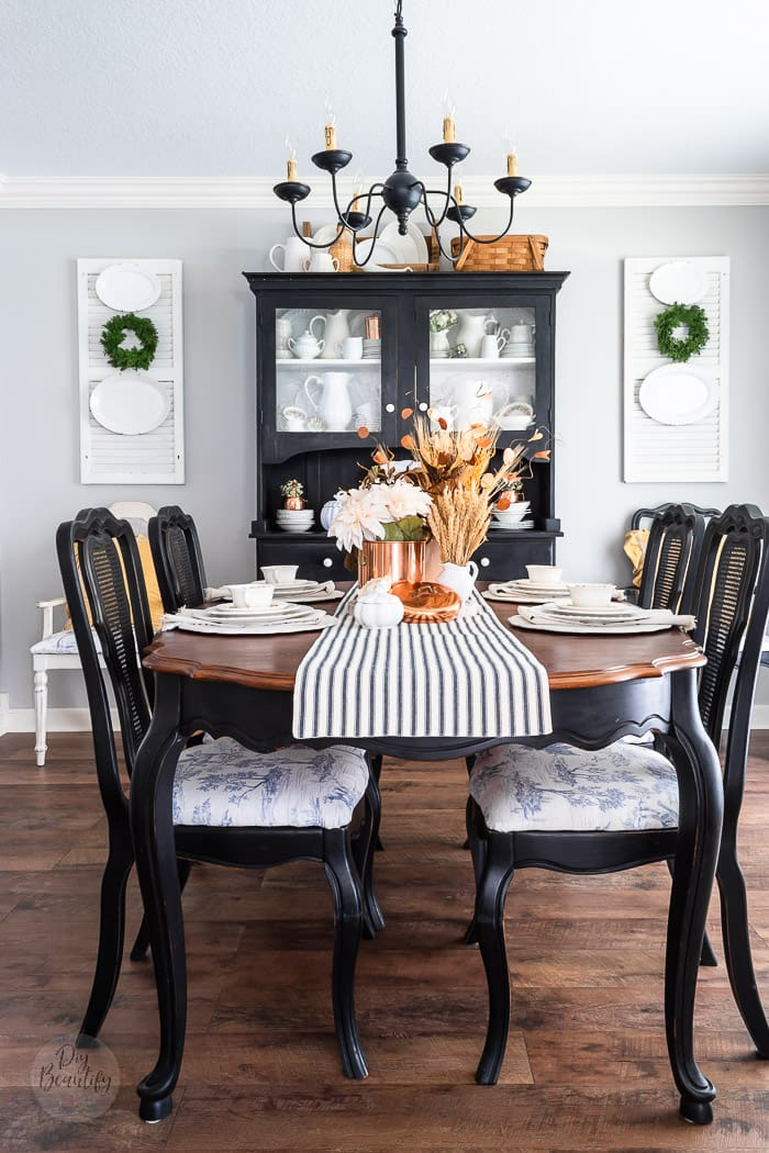 dining room with vintage black chairs and hutch, blue toile seats, shutters, white ironstone and warm fall colors