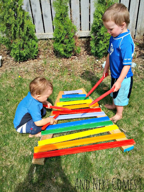 Two kids playing on a partially assembled DIY outdoor xylophone