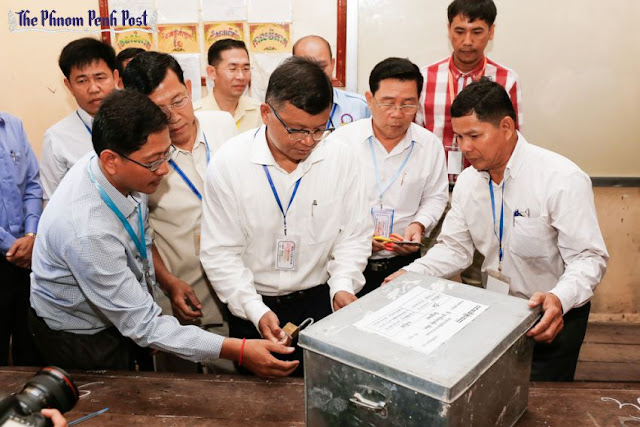 Education Minister Hang Chuon Naron (centre) unlocks a box containing test papers yesterday at Phnom Penh's Sisowath High School during the commencement of the nationwide Grade-12 exams. Pha Lina