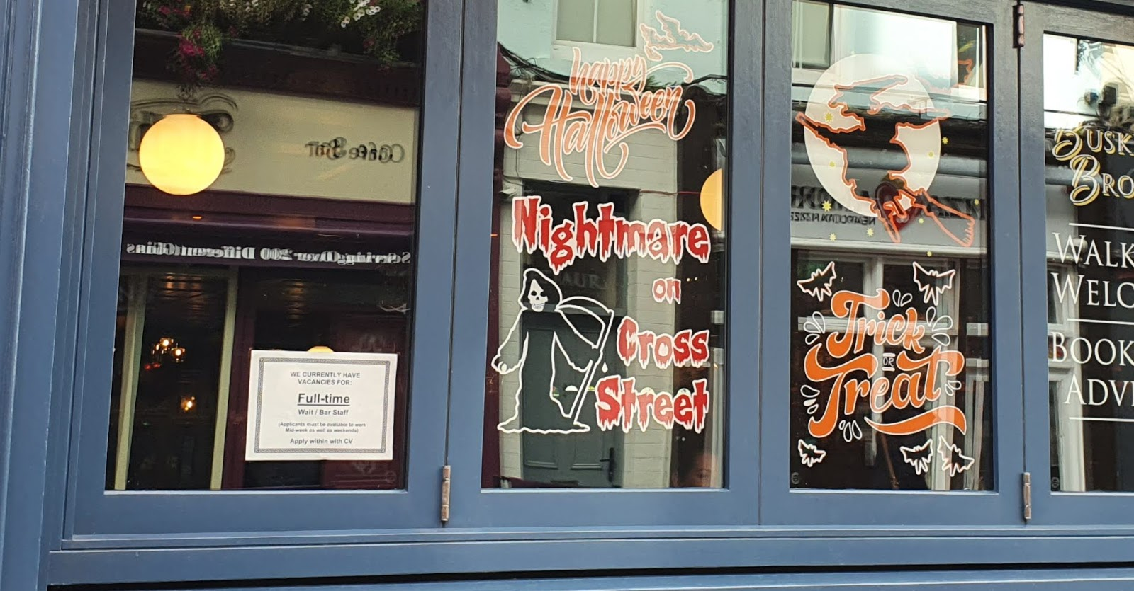 Restaurant window with job ad and Halloweeen decorations including a witch with axe, and captioned Nightmare on Cross Street