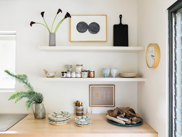 open shelves in kitchen with collected antique and art pieces and black cutting board